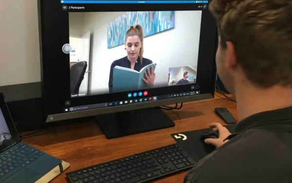 man participating in telehealth video conference with staff member