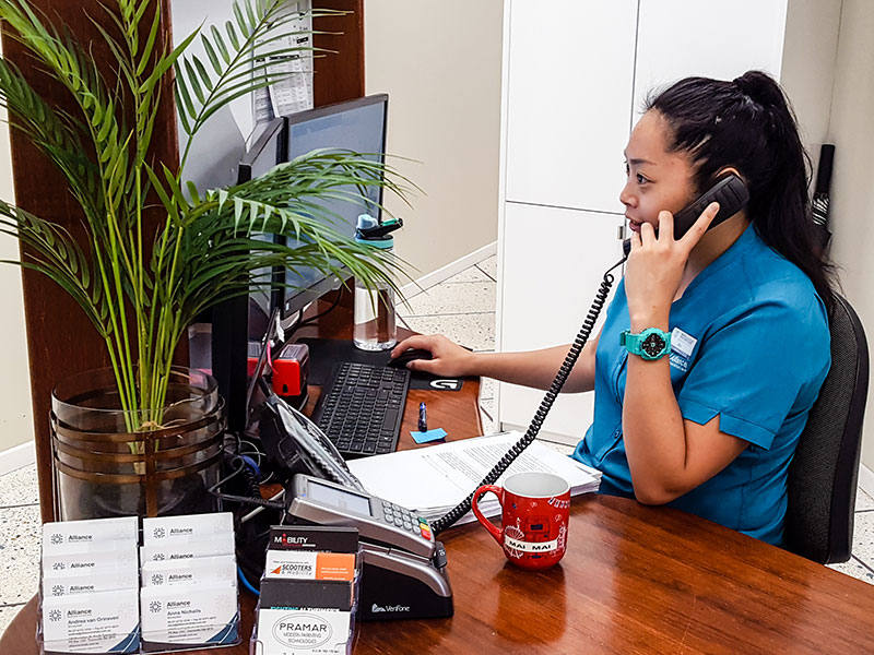 Receptionist on phone at Alliance Rehabilitation Townsville