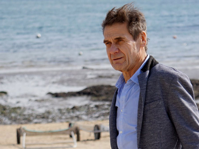 Windswept old man with beach in background