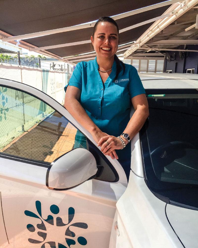 Smiling female driving trainer standing behind open car door