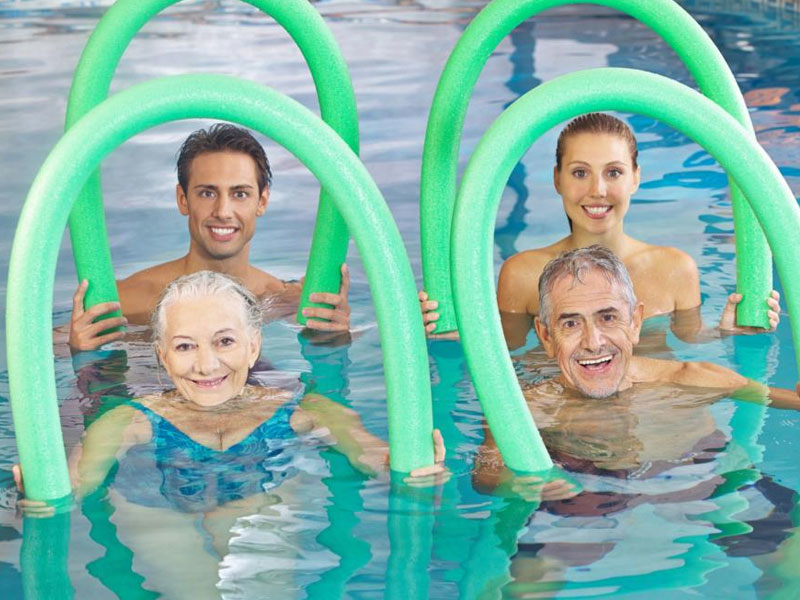 Four smiling people in hydrotherapy holding flotation devices