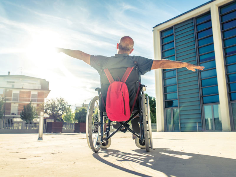 NDIS man in wheelchair with arms out