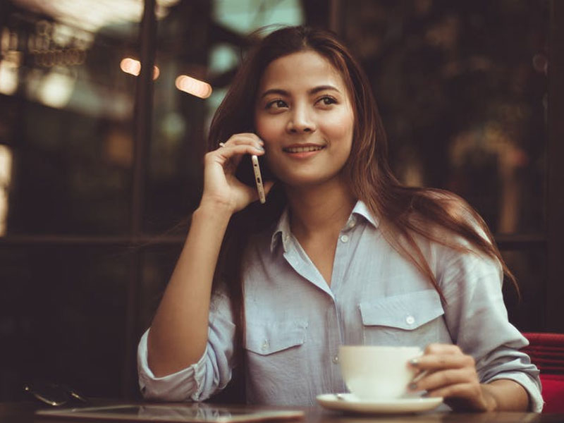 Woman speaking on telephone at a cafe