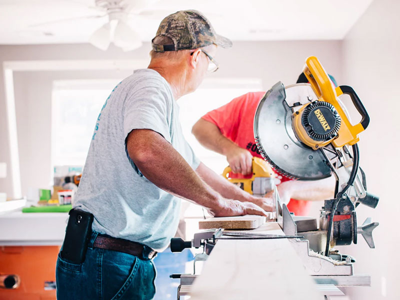 Old man cutting with a benchsaw