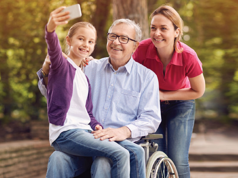 Happy man in wheelchair with family